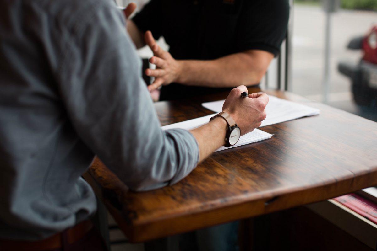 två män sitter och diskuterar vid ett bord och antecknar