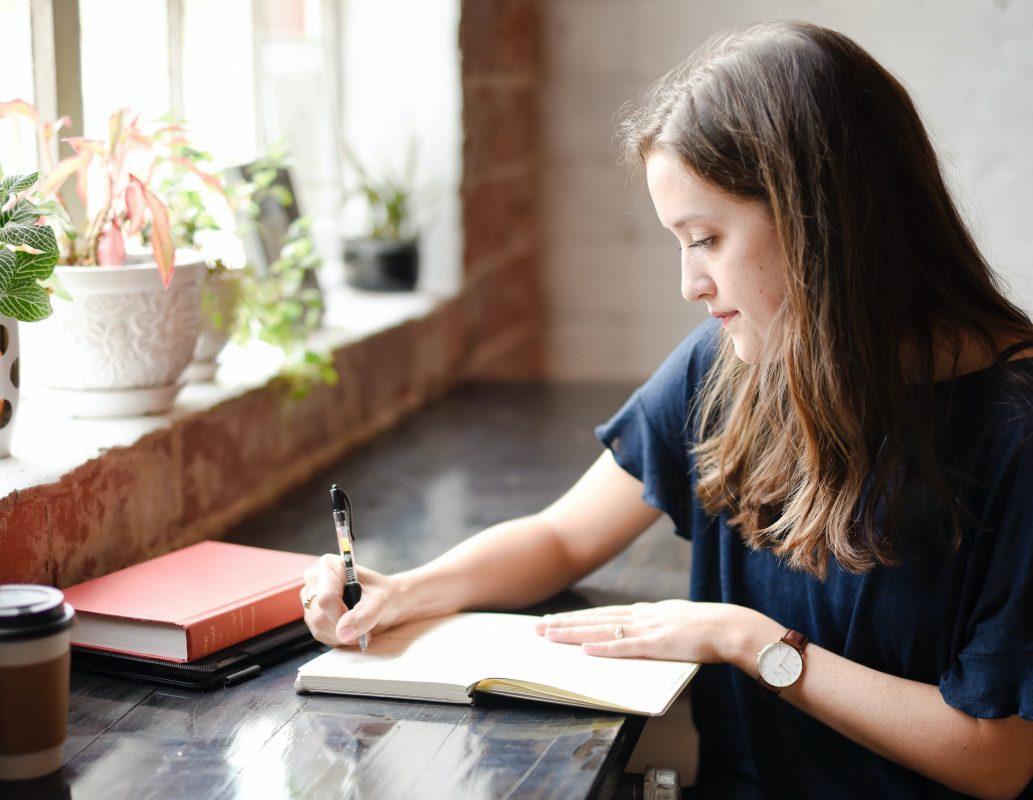 tjej som sitter och skriver i ett block