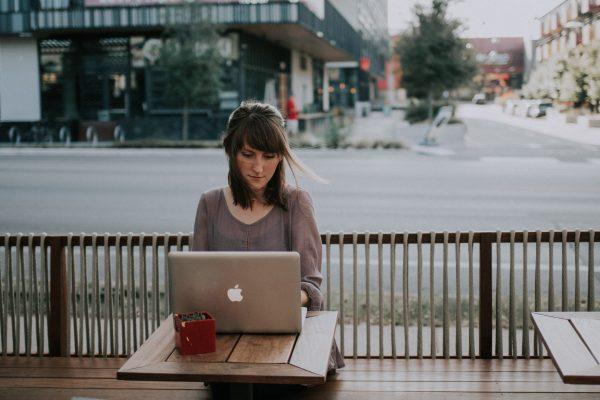 kvinna i grå skjorta sitter vid bord med sin MacBook
