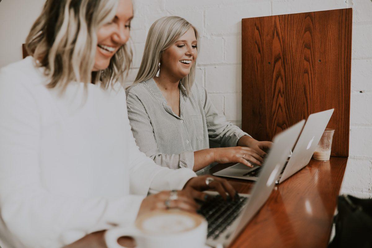 två kvinnor använder MacBooks och skrattar