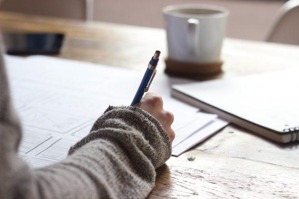 person med grå tröja sitter och skriver med blå penna